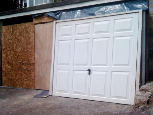 A real door (the wooden one on the left) partly concealed by a fake door (the garage door is going to be scrapped).