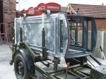 My K6 horizontal on the trailer. A queue of phone boxes in various stages of repair stands behind.
